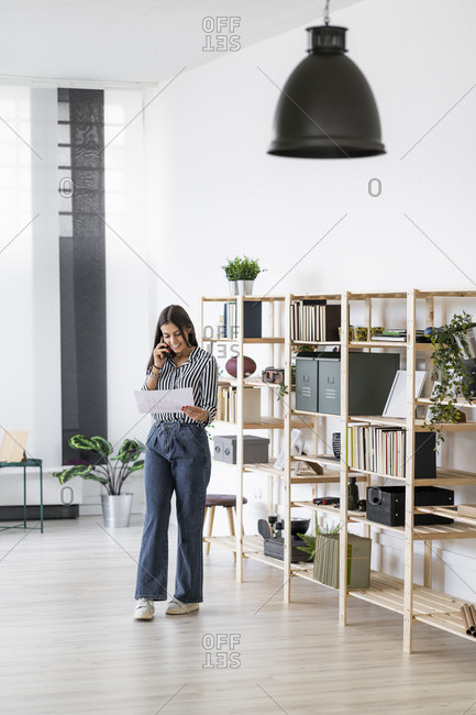 Smiling businesswoman talking on mobile phone while looking at plan standing against rack in office