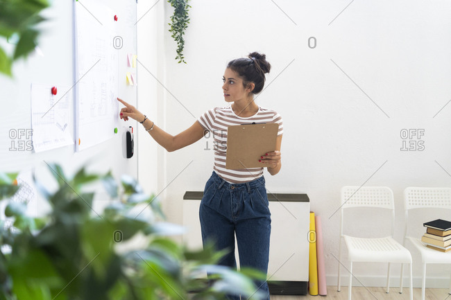Young businesswoman pointing at whiteboard while holding clipboard in creative workplace