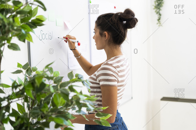 Young female design professional writing on whiteboard while planning strategy at creative workplace