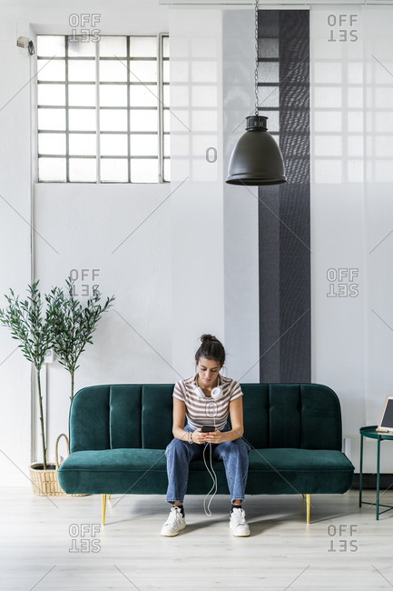 Female architect using smart phone while sitting on sofa at creative workplace