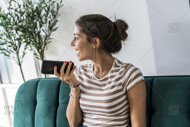 Cheerful female architect talking through mobile phone while sitting on sofa at office