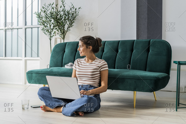 Thoughtful female architect sitting cross-legged on floor while using laptop against sofa at office