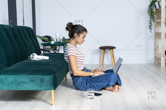 Confident female architect using laptop while sitting cross-legged on floor against sofa at office