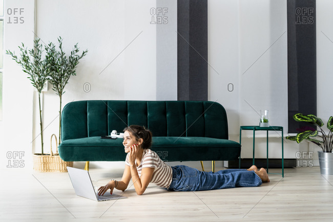 Thoughtful female architect looking away while lying with laptop on floor by sofa in creative workplace