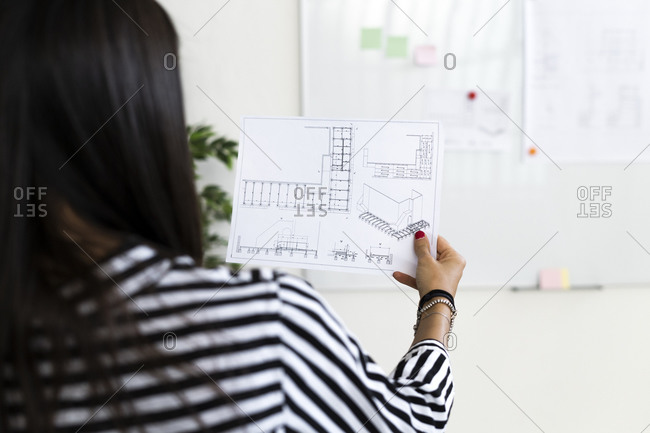 Female architect analyzing floor plan on paper at creative workplace