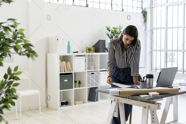 Young female design professional examining plan at desk while working in creative office