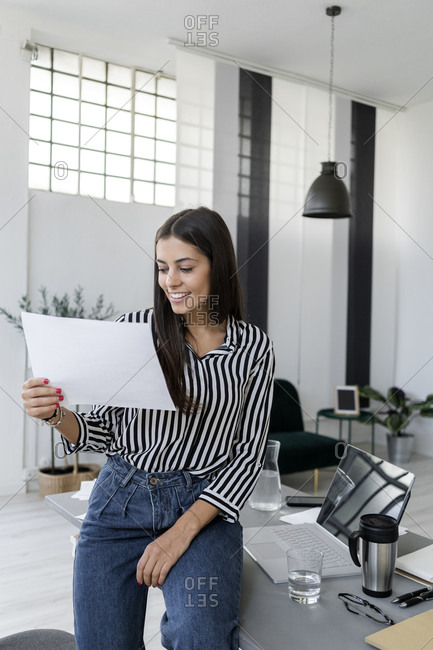 Smiling young female architect holding plan while sitting at desk in creative office