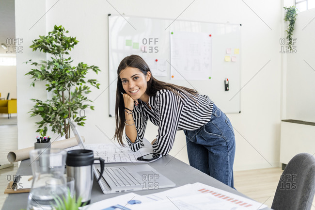 Happy young female architect with floor plan leaning on desk while working at creative office