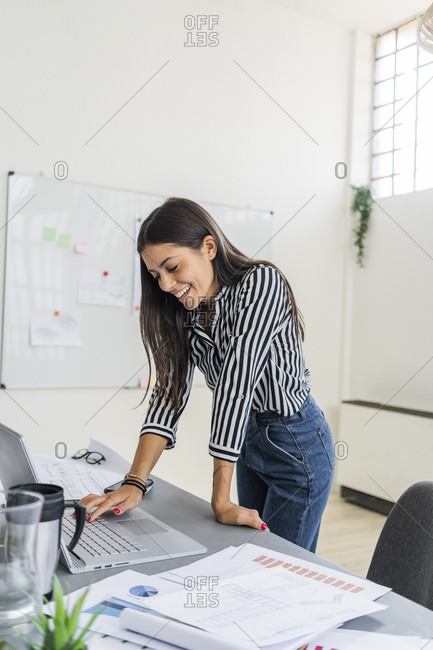 Smiling young female design professional using laptop at desk while working in creative office