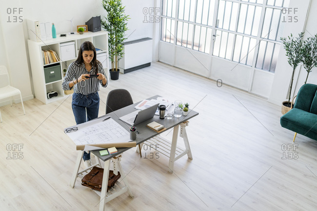 Female architect photographing blueprint at desk in creative workplace