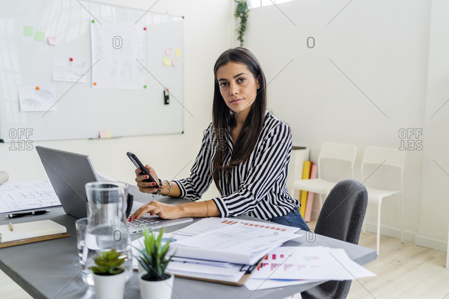 Confident female design professional sitting with wireless technologies at desk in office