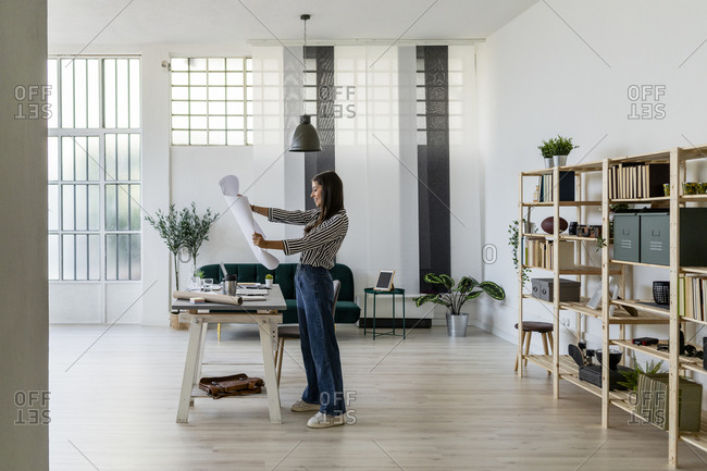 Smiling young female architect looking at blueprint while standing against rack in office