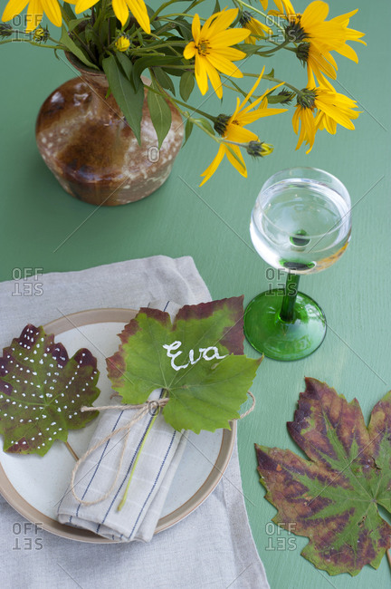 Wineglass with water- vase with blooming Jerusalem artichokeflowers and name tag made of autumn leaf