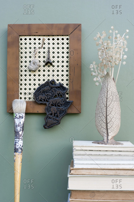 DIY picture frame with wicker rack holding various mementos- stack of books- paintbrush and vase with dried plants