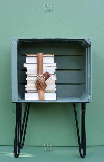 Books kept in green color crate with hairpin leg against turquoise colored background