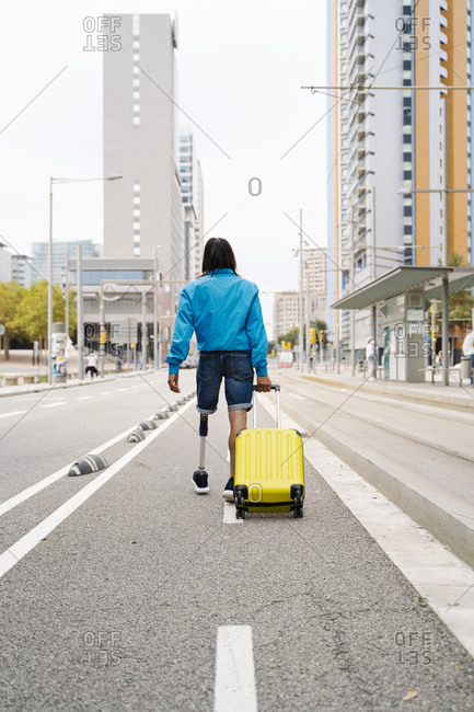 Young man walking with luggage on road in city