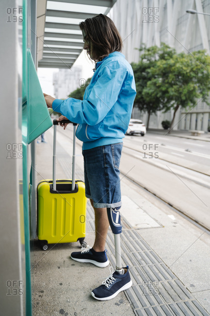 Young man buying ticket from ticket machine while standing at railroad station