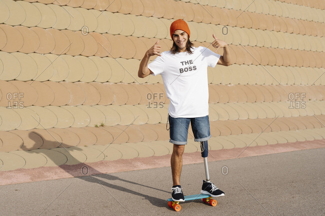 Young disabled man standing on skateboard at sports court