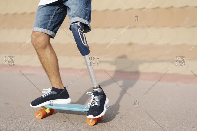 Athlete with artificial limb and foot standing on skateboard at court