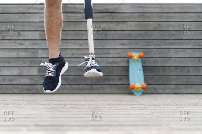 Young man with artificial limb and foot jumping against wall