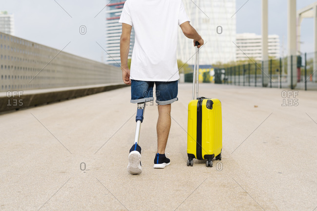 Disabled young man walking with luggage at sidewalk in city