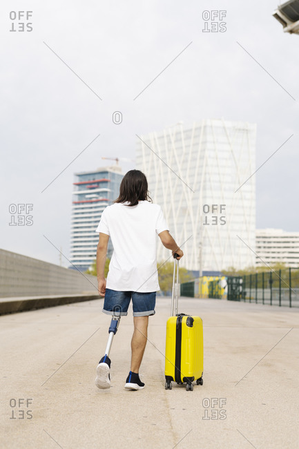 Disabled man walking with luggage at sidewalk in city