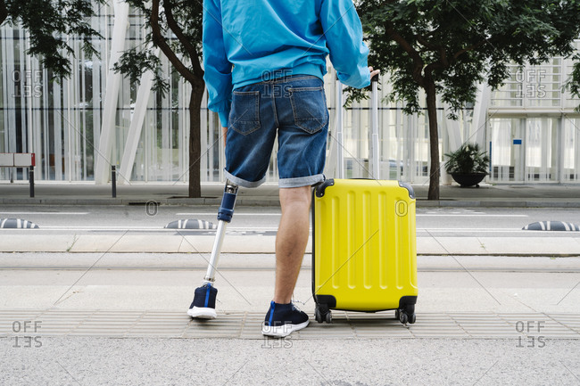 Disabled man with luggage standing at railroad station