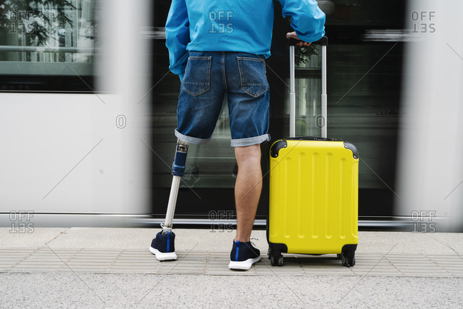 Young man with artificial limb and foot standing by luggage at railroad station