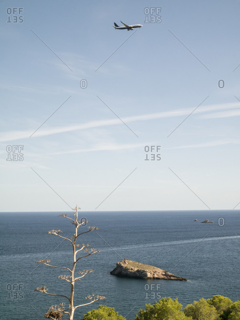 Commercial plane flying over sea with clear line of horizon in background