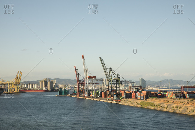 Spain- Province of Barcelona- Barcelona- Clear sky over commercial dock at dusk