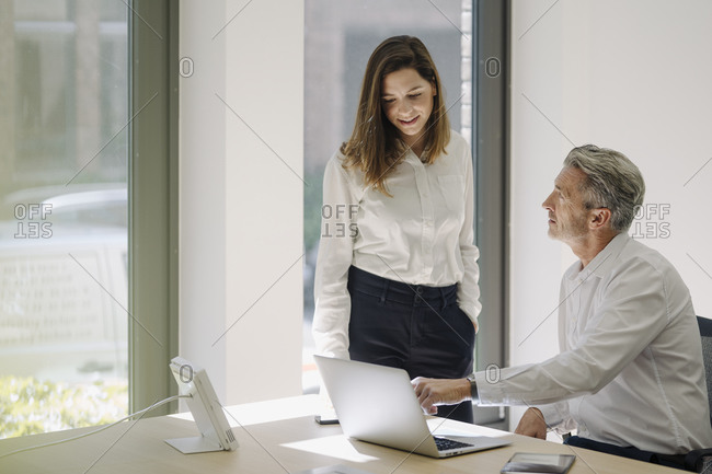 Businessman pointing at laptop while sitting on chair by woman at office