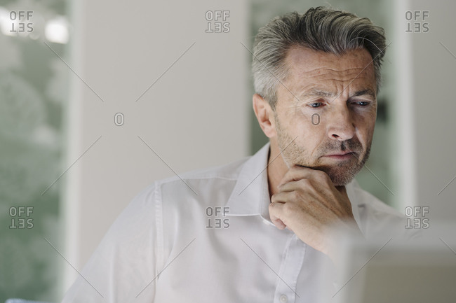 Thoughtful man with hand on chin sitting at office