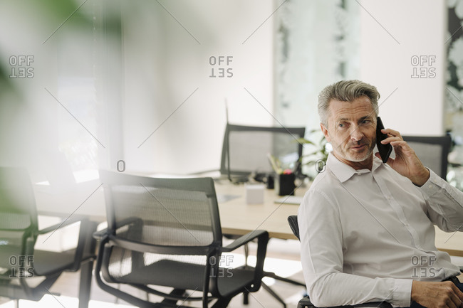 Businessman talking on phone while sitting on chair at office