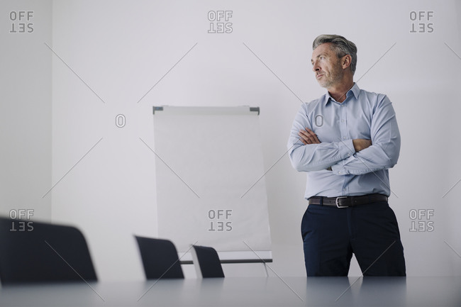 Businessman with arms crossed standing in board room at office