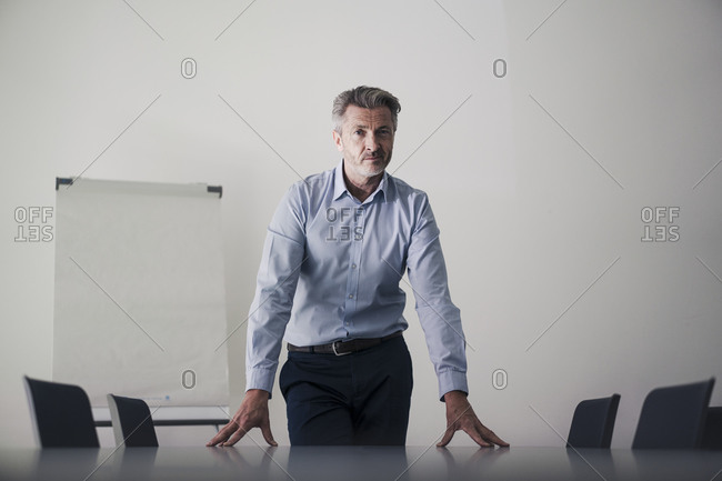 Man standing with hands on table in board room at office