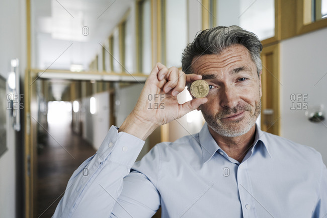 Businessman covering eyes with bitcoin while standing at office