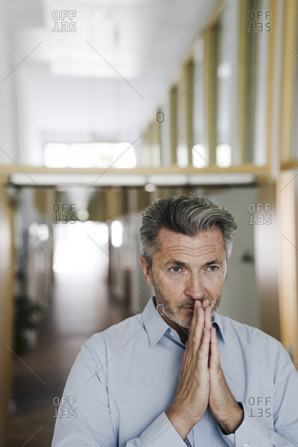 Businessman with hands clasped standing at office corridor