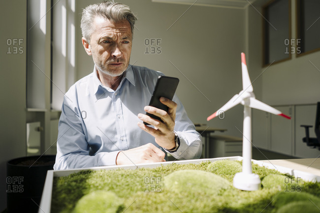 Businessman taking photo of wind turbine toy and moss frame while sitting at office