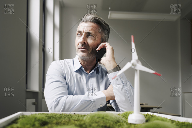 Businessman on the mobile phone sitting by moss frame and wind turbine toy at office