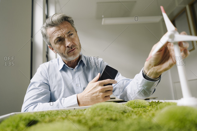 Man looking at wind turbine toy over moss frame while sitting at office