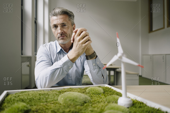 Businessman with hands clasped sitting by wind turbine toy and moss frame on table at office
