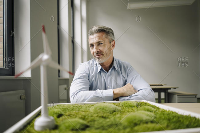 Smiling businessman sitting by wind turbine toy and moss frame on table at office