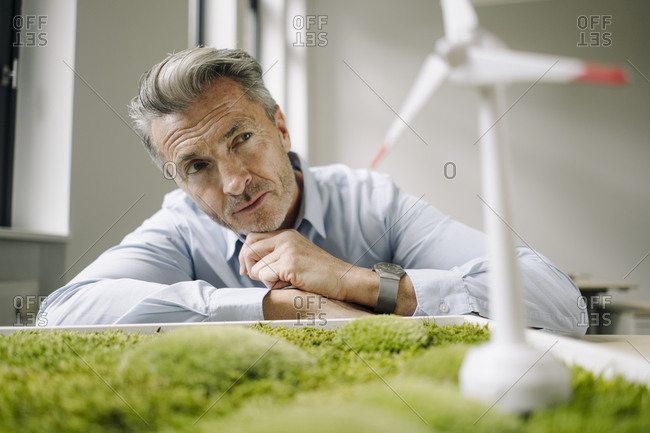 Businessman looking at wind turbine toy over moss frame while leaning on table at office