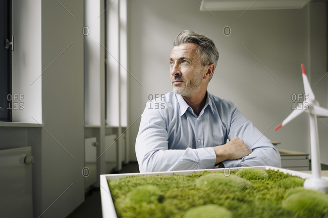 Businessman looking away while sitting by wind turbine toy and moss frame at office