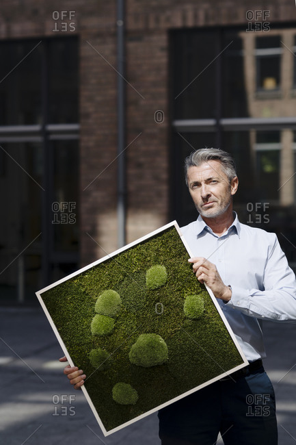 Businessman holding moss frame while standing against building