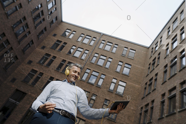 Happy man with headphones and digital tablet dancing while standing against building exterior