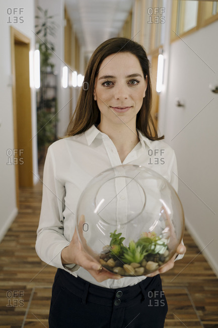 Smiling businesswoman holding botany in hand while standing at office corridor