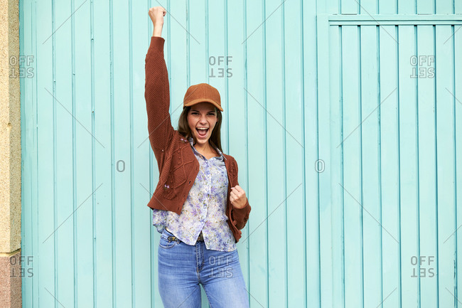 Young woman with hand raised screaming while standing against blue metal door
