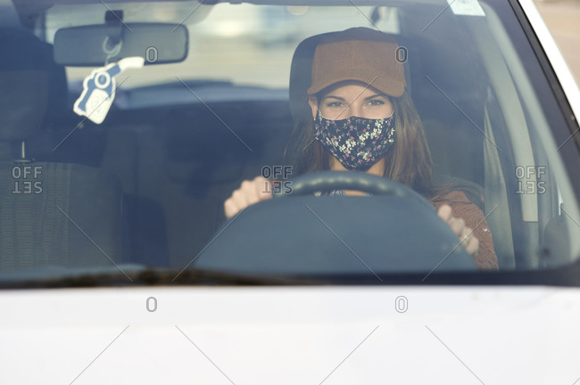 Young woman wearing face mask driving car in city
