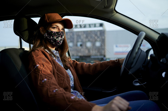 Young woman with cap and face mask driving car in city